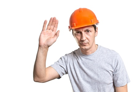 the young worker in a helmet shows a greeting sign Stock Photo - 17794618
