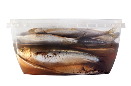 the salted sprat in a plastic box, it is isolated on the white Stock Photo - 18625043