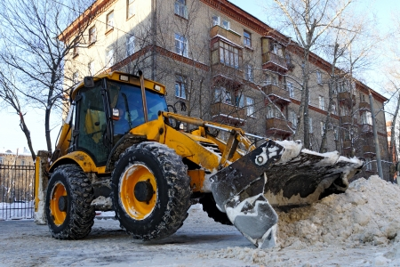 Tractor removes snow on city street. photo