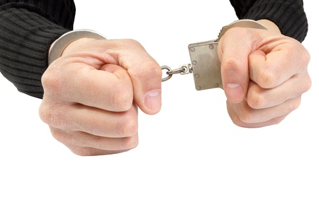 Hands in handcuffs squeezed in a fist  Stock Photo - 18722785