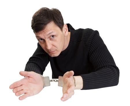 interrogatively: The man in handcuffs interrogatively looks