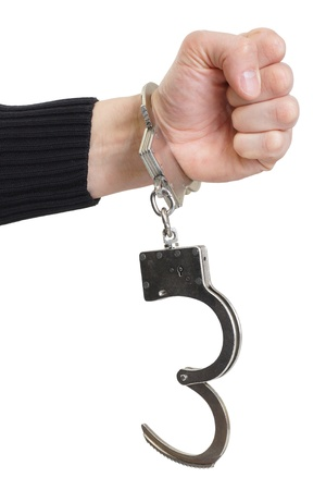 Hand in handcuffs squeezed in a fist  Stock Photo - 18722782