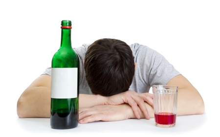 the young man sleeping at a table and a bottle with wine photo