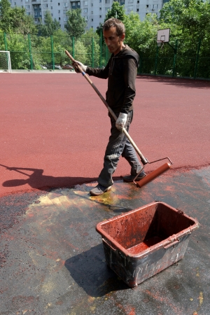 06 06 2013 Moscow  Workers put a rubber polyurethane covering on the sports ground  Stock Photo - 22888412