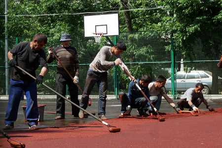 06 06 2013 Moscow  Workers put a rubber polyurethane covering on the sports ground  Stock Photo - 22888431