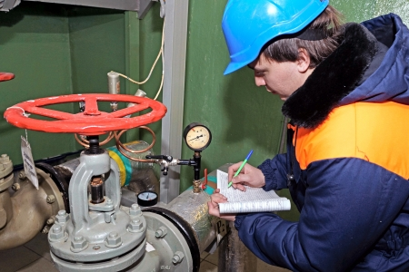The worker writes down monometer data on water pipes. photo