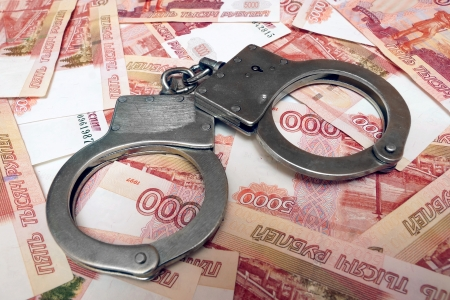 Banknotes and metal handcuffs Stock Photo - 24259459