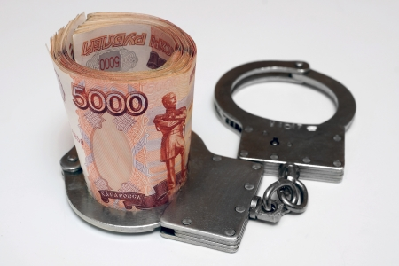Banknotes and metal handcuffs Stock Photo - 24259324