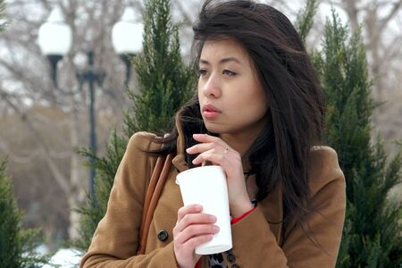 the Asian girl in a coat with drink in hands Stock Photo - 24748083