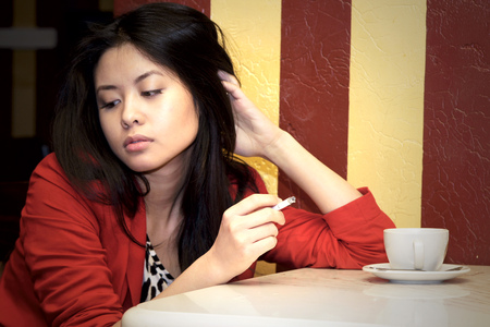 the Asian girl thoughtfully sits with a cigarette and a   coffee cup Stock Photo - 24748086