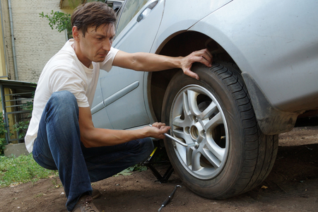 The man change the punctured wheel of the car. photo
