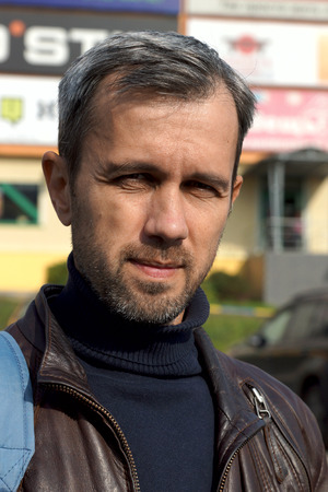 portrait of the gray haired unshaven man in a leather jacket