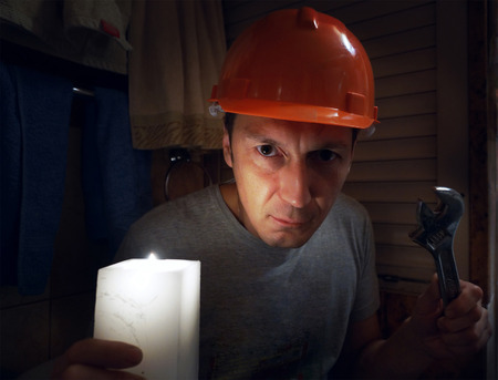 The plumber in a helmet with a nut key in the dark room. photo