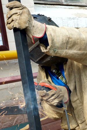 the welder welds a metal detail photo