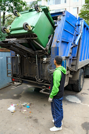 dump truck: Loading of the garbage container, real photo. Stock Photo