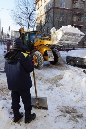 clean street: a man with a shovel looks like a tractor clears snow