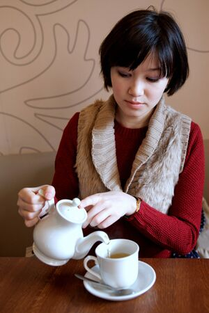 pours: Woman pours tea into a Cup from the kettle.