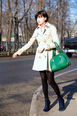 mujer bonita: Chica coge un taxi en la carretera. Vertical de la imagen.