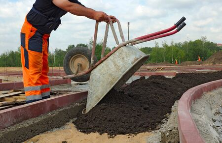 hombres trabajando: Trabajador vierte el suelo de la carretilla.