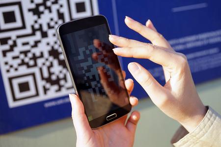 La fille scanne le code QR avec un téléphone mobile intelligent. Banque d'images - 50396585