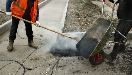unload: Workers unload the asphalt from wheelbarrow Stock Photo