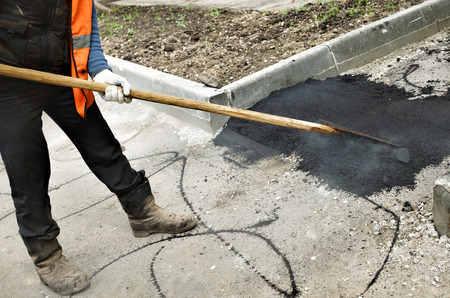 Work leveled hot asphalt on the repaired road. Stock Photo