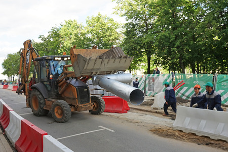 beautification: MOSCOW, RUSSIA - MAY 15, 2016: Bulldozer carrying a metal pipe. Reconstruction of the roadway within the city beautification program My Street in Moscow.