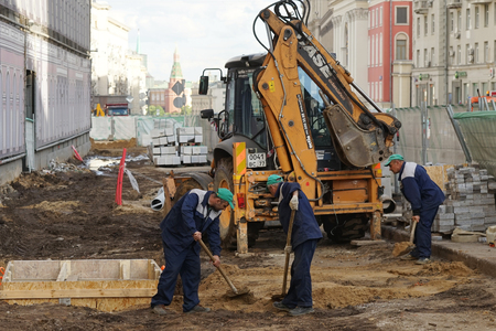 construction workers: MOSCOW, RUSSIA - MAY 15, 2016: Building machinery and workers with shovels. Reconstruction of the roadway within the city beautification program My Street in Moscow. Editorial