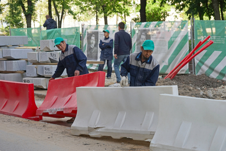 beautification: MOSCOW, RUSSIA - MAY 15, 2016: Asian workers install a road fencing. Reconstruction of the roadway within the city beautification program My Street in Moscow.