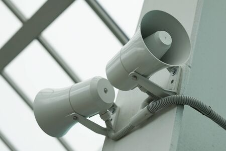 public address: Two twin megaphone on the wall of a building.