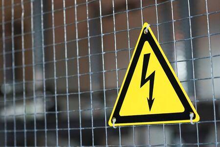 metal mesh: Metal mesh and yellow electrical danger sign. Stock Photo