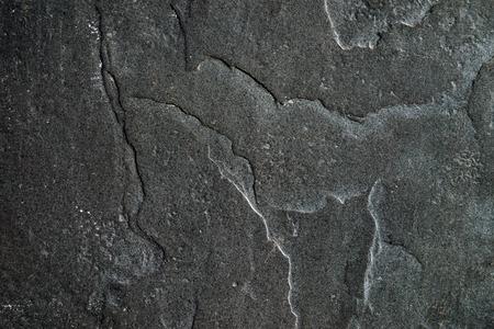 Stenen muur met verf bijna zwart, met sporen van ouderdom.