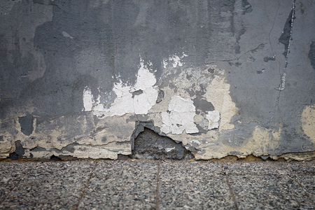 granite wall: Old painted wall with crumbling plaster and cracks. The picture at the level of the granite floor. Stock Photo