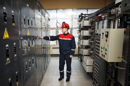 Electricians in protective helmet and blue working uniform, Located next to the control board and controls the operation of electric power station. Stock Photo