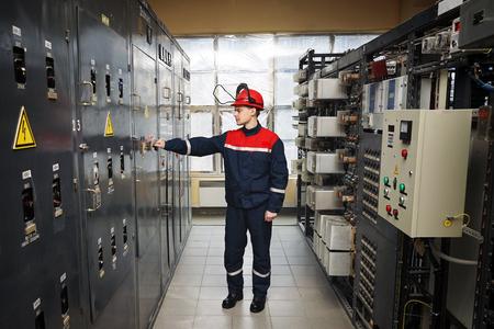 Elektriciens in beschermende helm en blauw werkend uniform, Gelegen naast het bedieningspaneel en controleert de werking van het elektriciteitscentrale.