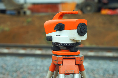 geodetic: Orange theodolite, geodetic device in the wild, close-up. Stock Photo