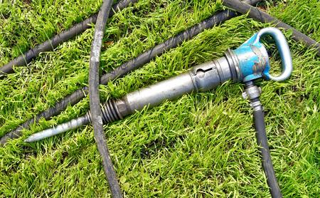 Jackhammer on a green lawn