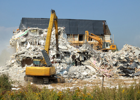 Dismantling of concrete structures, excavators break down old buildings