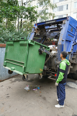 MOSCOW, RUSSIA - August 16, 2016: Work janitors change the filled garbage container in the trash dump. Loading a garbage truck in Moscow. Editorial