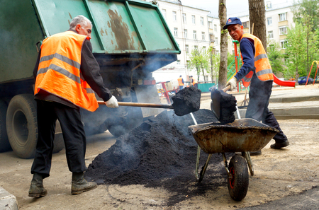 MOSCOW, RUSSIA - MAY , 2011: Workers with shovels and a pile of asphalt. The program of renovation of public areas in Moscow. Editorial