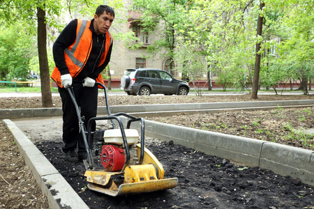 MOSCOW, RUSSIA - MAY , 2011: Man with a vibrator for asphalt. The program of renovation of public areas in Moscow.
