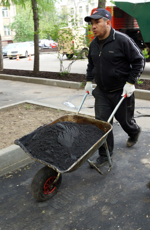 MOSCOW, RUSSIA - MAY , 2011: A man with a wheelbarrow, black fresh asphalt. The program of renovation of public areas in Moscow.