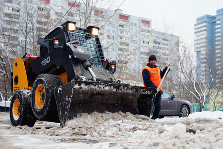 MOSCOW, RUSSIA - January , 2015: Mini bulldozer and worker, remove the snow. Cleaning the streets of the city in winter in Moscow.