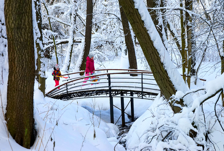 MOSCOW, RUSSIA - JANUARY, 2019: Mother and daughter have fun walking over the bridge, winter park, frosty day, frozen river, trees in the snow. Éditoriale
