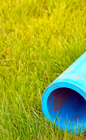 Plastic water pipe on a green lawn.