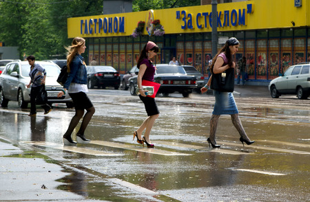 MOSCOW, RUSSIA - SEPTEMBER, 2018: Young girls cross the road, it is raining, wet asphalt.