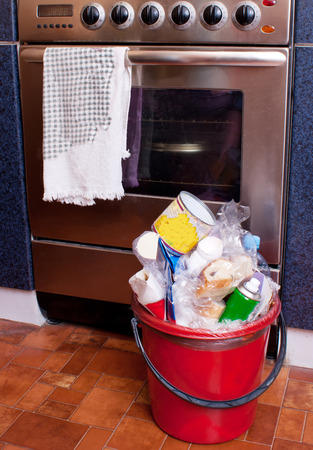 Trash bin in the kitchen next to the electric stove. Stock Photo
