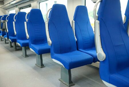 Empty new seats in the train, covered with blue cloth.
