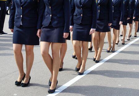 Women in militarized uniform march in formation. Feminine legs in black shoes.