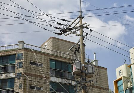 Jeju island, South Korea - April 2018: Electric posts with wires on the streets of the city in Jeju. 新聞圖片